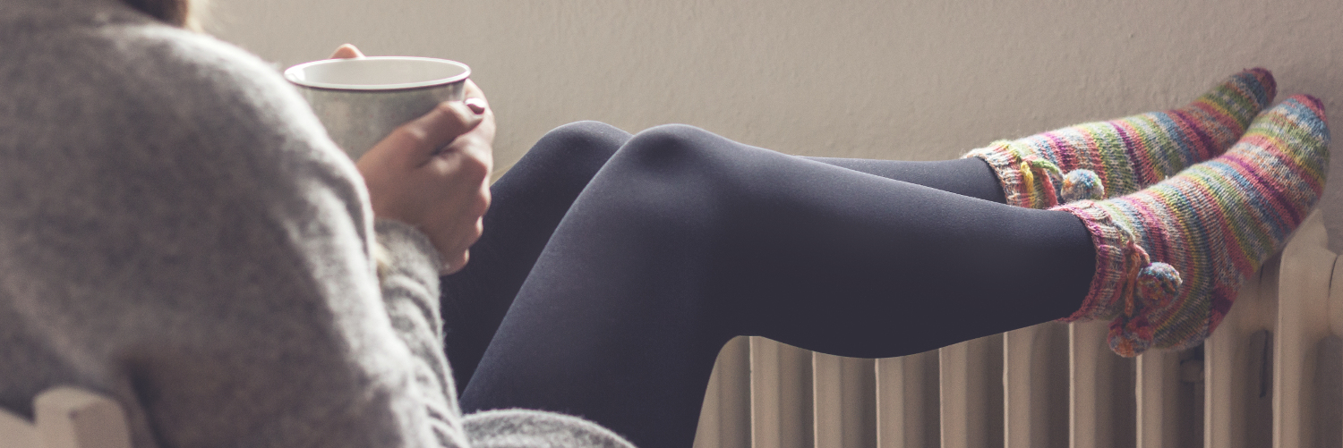 Woman warms her feet on a radiator and thinks about combi boiler prices